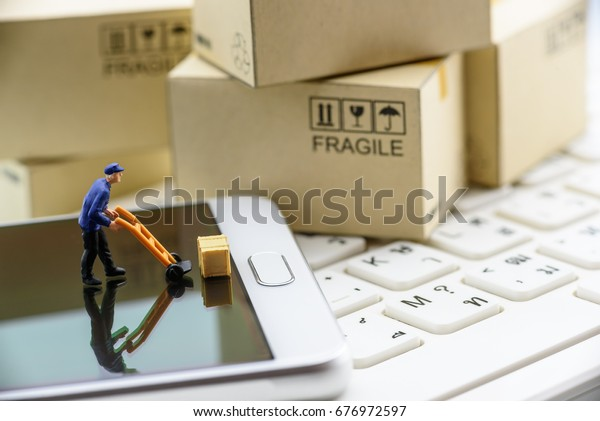 Miniature figurine postman picks up a wood crate on a white smart phone with small light brown paper boxes behind. Concept of transportation that grew very fast due to the popularity of the internet.