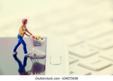 Miniature figurine of a shopper pushes a shopping cart on smarthphone. Concept of brick and mortar stores nowadays face with increased competition from online ecommerce and decreasing in foot traffic.