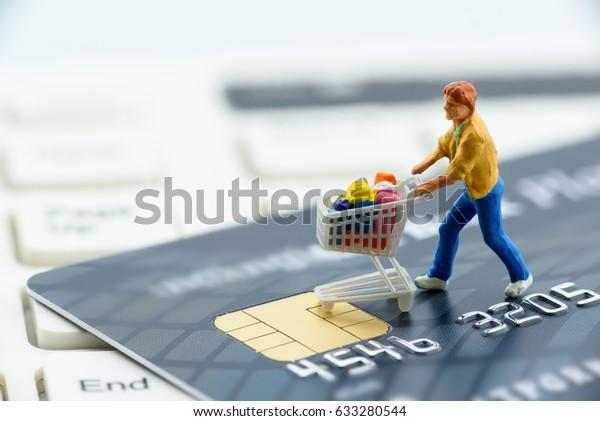 ミニチュアの置物:買い物客は、スマートクレジットカードとキーボードにショッピングカートを押す。現在のブリック・モルタル店のコンセプトは、インターネット上での電子商取引との競争が激化している。