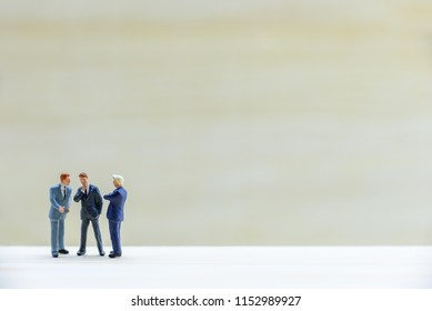 Miniature figurine top management team e.g CEO, CFO, COO discuss, talk or have dialogue / make decision on company financial report and performance. Blank space for text, graphic or other information.