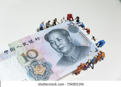 Miniature figurine toys holding ten Chinese Yuan (Renminbi - CNY) notes - slave to money and work concept. Focus on the portrait of President Mao Ze dong.