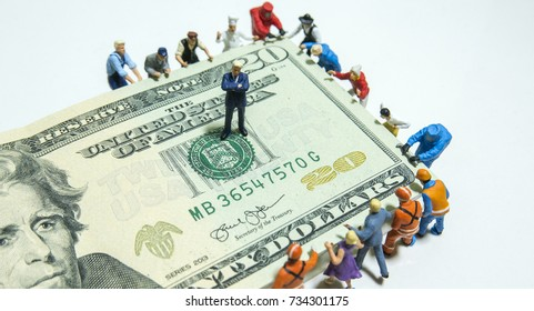 Miniature figurine toys holding US twenty dollar notes - slave to money and work concept. Focus on the businessman.