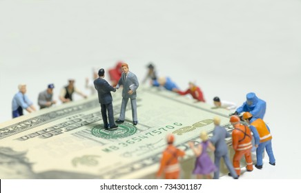 Miniature figurine toys holding US twenty dollar notes - slave to money and work concept. Focus on the businessmen in negotiation. Both shakes hands.
