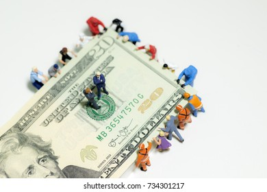 Miniature figurine toys holding US twenty dollar notes - slave to money and work concept. Focus on the businessmen in negotiation or deep discussion - top view.