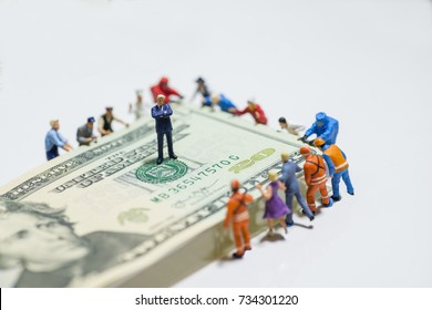 Miniature figurine toys holding US twenty dollar notes - slave to money and work concept. Focus on the businessman folding arms in the centre. Ruthless and slave to work concept.