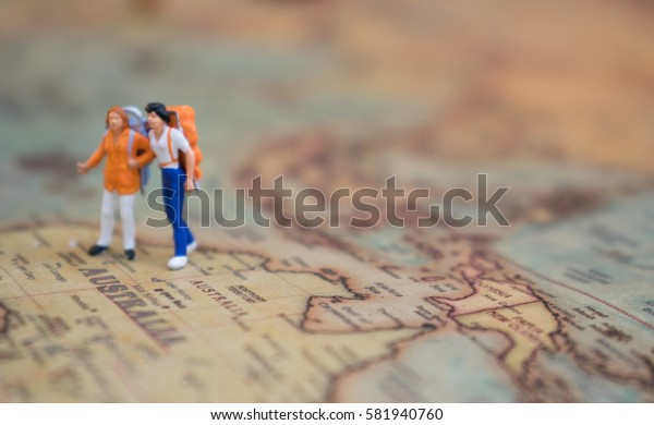 Miniature figurine of young traveler standing on big map , travel concept