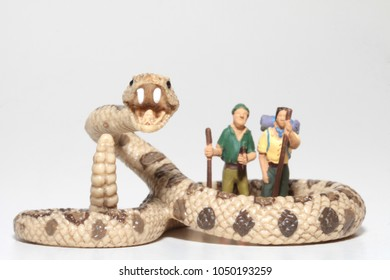miniature figurines of hikers with a giant snake
