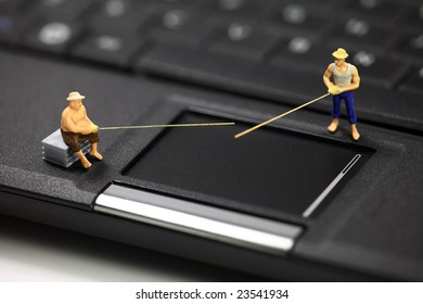 Miniature fisherman standing on a laptop computer representing online email phishing scams. Computer phishing and identity theft concept.