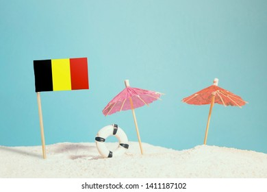 Miniature flag of Belgium on beach with colorful umbrellas and life preserver. Travel concept, summer theme.