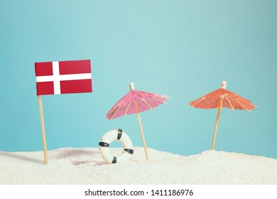 Miniature flag of Denmark on beach with colorful umbrellas and life preserver. Travel concept, summer theme.
