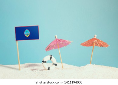 Miniature flag of Guam on beach with colorful umbrellas and life preserver. Travel concept, summer theme.