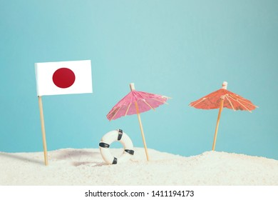 Miniature flag of Japan on beach with colorful umbrellas and life preserver. Travel concept, summer theme.