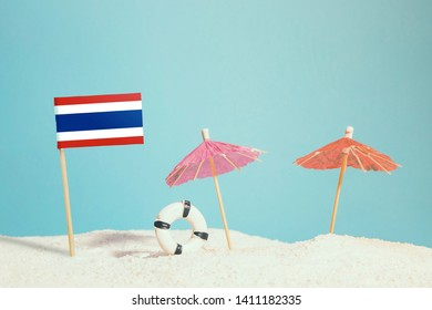 Miniature flag of Thailand on beach with colorful umbrellas and life preserver. Travel concept, summer theme.