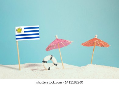 Miniature flag of Uruguay on beach with colorful umbrellas and life preserver. Travel concept, summer theme.