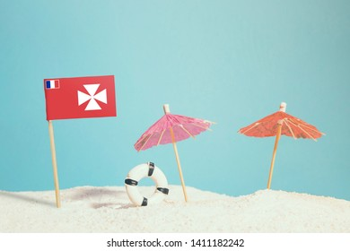 Miniature flag of Wallis And Futuna on beach with colorful umbrellas and life preserver. Travel concept, summer theme.