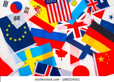 Miniature flags of different States are lying haphazardly on the table. Official symbols of States. The concept is a political map of the world. Variety of flags of States.