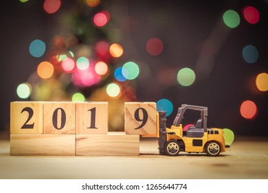 Miniature forklift lift up year 2019 wooden block on christmas background