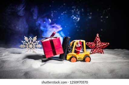Miniature Gift Box by Forklift Machine on snow ,Determined Image for Christmas Holiday and Happy New Year Gift Celebration concept. Selective focus