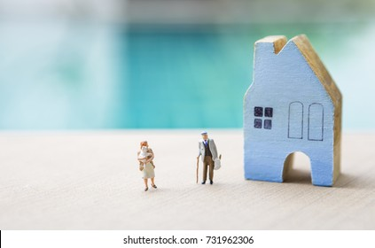 Miniature girl holding baby with miniature old man carry grocery bag with blue wooden house over blurred blue background
