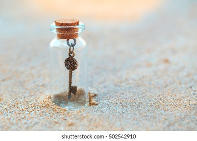 Miniature glass bottle with metal vintage key inside on gold sand background. Enigmatic concept, key to something.