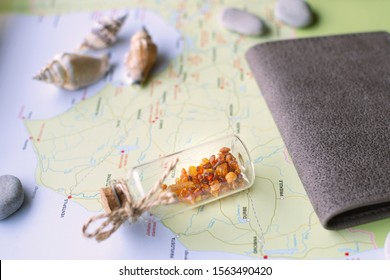 Miniature glass jar with amber, passport in a leather cover, some stones and sea shells are lying on a map of Latvia (fragment). Concept of natural  travel souvenirs from Baltic countries.