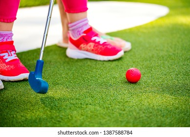 Miniature golf outdoor. Little caucasian girl golfing in the mini golf course. Close-up photo, selected focus.