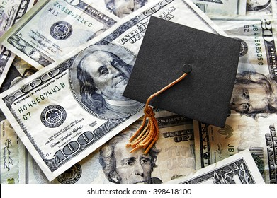 Miniature graduation cap on hundred dollar bills