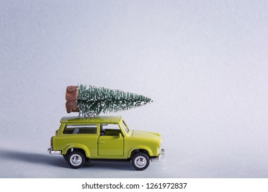 Miniature green car with christmas tree on is top