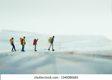 miniature group of backpacker traveling and journey on the map