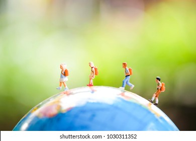 Miniature Group of Student walking around the world use as new technology social network , study aboard and education concept.
