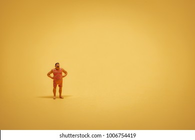Miniature guy in retro swimsuit on yellow backgound with some copyspace.