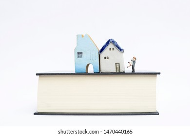 Miniature happy couple and design miniature house on thick book isolate on white background, marriage plan, property and real estate business rule and insurance concept