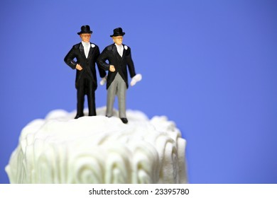 Miniature homosexual couple standing on top of a wedding cake. Gay/same sex marriage concept.