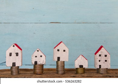 Miniature house and coins on the wooden table and blue paint background