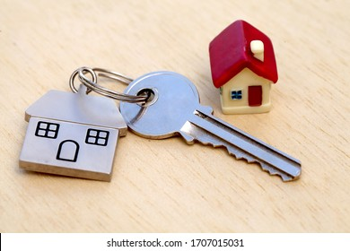 Miniature house and key on wooden background