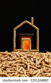 Miniature house made with wood pellets. Heating concept with combustion chamber in the background.