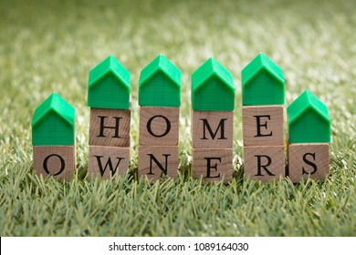Miniature House Model Over Wooden Block Showing Home Owners Text On Green Grass