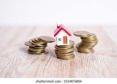Miniature house models and stacked coins Near each other, scattered coins Business risk management concepts Real estate investment and home mortgages, financial real estate concepts