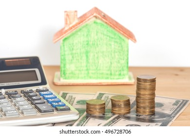 Miniature house with money and office supplies