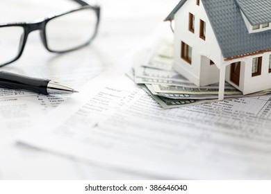 Miniature house with money on tax papers.