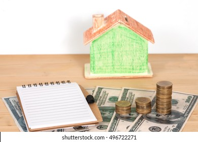 Miniature house with money  to the sale or purchase of Real Estate