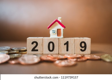 Miniature house on new year wooden block number with stack coins using as business, financial and property concept