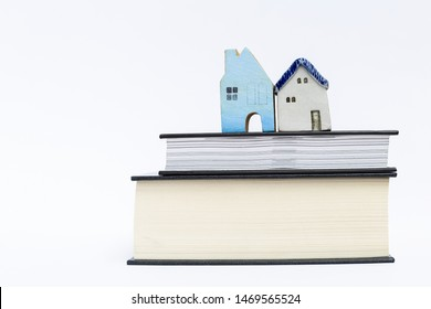 Miniature house on thick book isolate on white background, property and real estate business and legal also rule, house insurance and house manual