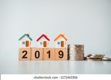 Miniature house on wooden block year 2019 with stack coins using as business and property concept