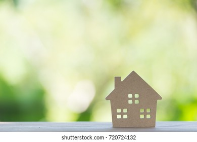miniature house  on wooden mock up over blurred green garden on day noon light.Image for property real estate investment concept.