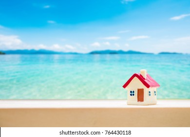miniature house with red roof on tropical sand beach over blurred cloudy sky on day noon light.Image for property real estate investment concept.