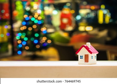 miniature house with red roof on wooden mock up over blurred Christmas decoration background.Image for property real estate investment concept.
