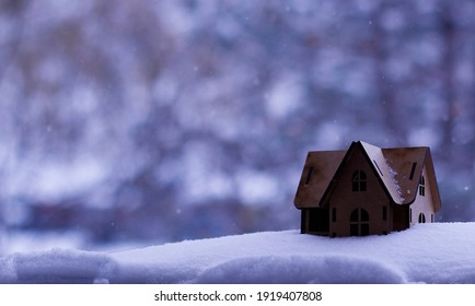 Miniature house in the snow and miniature human and deer figure
