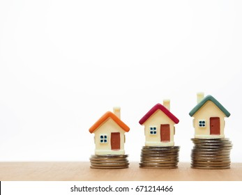 Miniature House with Stack Coins on Table with White Background. : Home Loan, Mortgage, Save Money, Insurance and Real Estate Investment Concept.