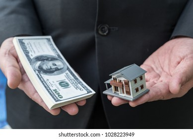 Miniature house toy and money in man's hands.Mortgage concepts.